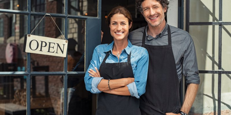 Casal em frente a uma loja com a placa de aberto. Imagem ilustrativa texto franquias pouca concorrência