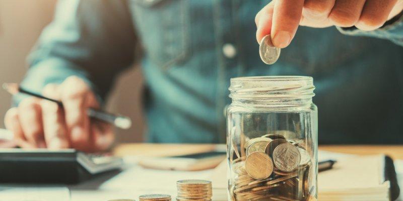 Homem colocando moedas em um pote com calculadora ao lado e monte de moedas em escadinha do mesmo lado, mais a frente. Imagem ilustrativa texto franquias sócios famosos