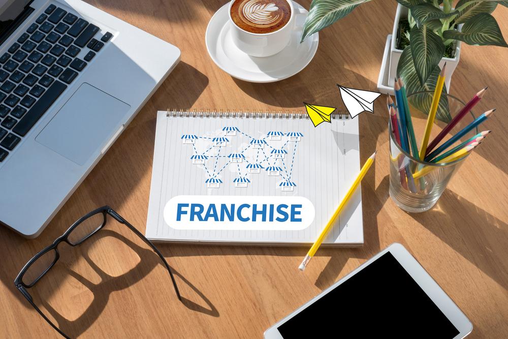 Caderno escrito franchise com desenho de várias lojas pelo globo. Ao lado computador, tablet, oculos, café e alguns lápis. Imagem ilustrativa texto franqueamento.