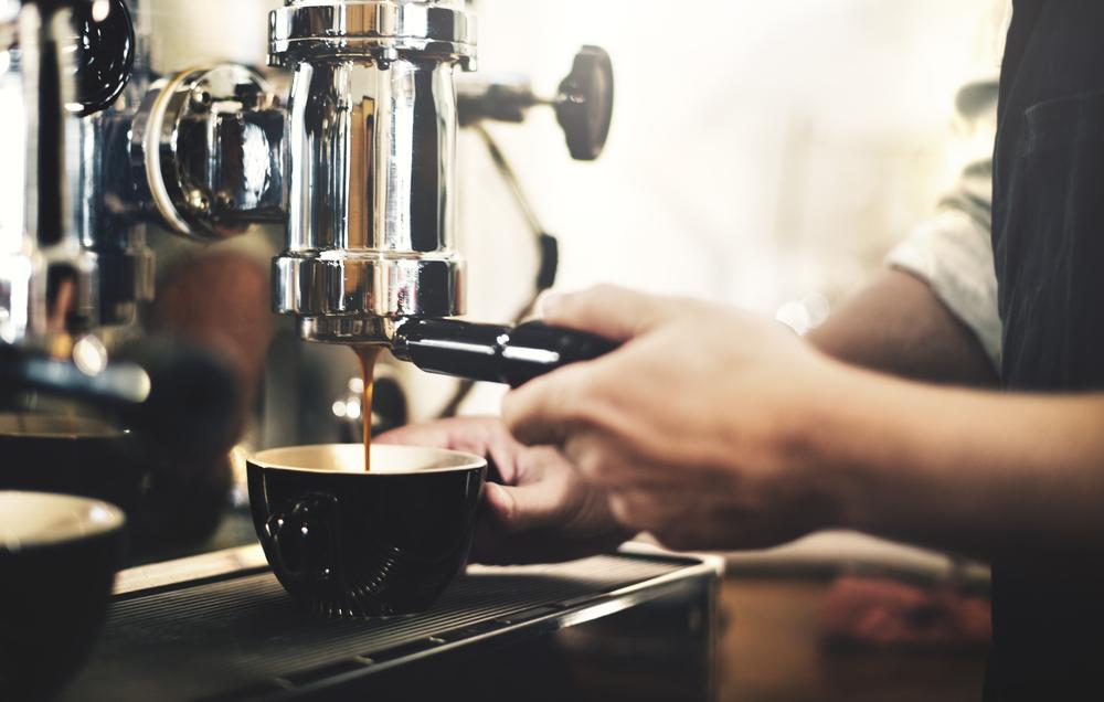 Vemos uma mão masculina fazendo café em uma loja (imagem ilustrativa). Texto: franquia am pm mini market.