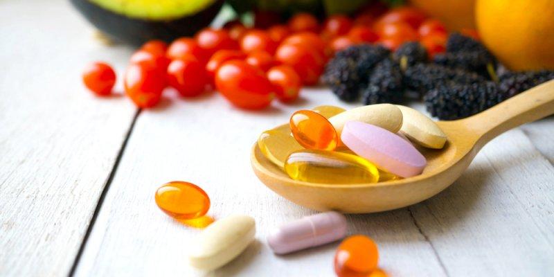 Vários comprimidos numa colher de madeira ao lado de frutas e verduras. Imagem ilustrativa texto franquia bioflora