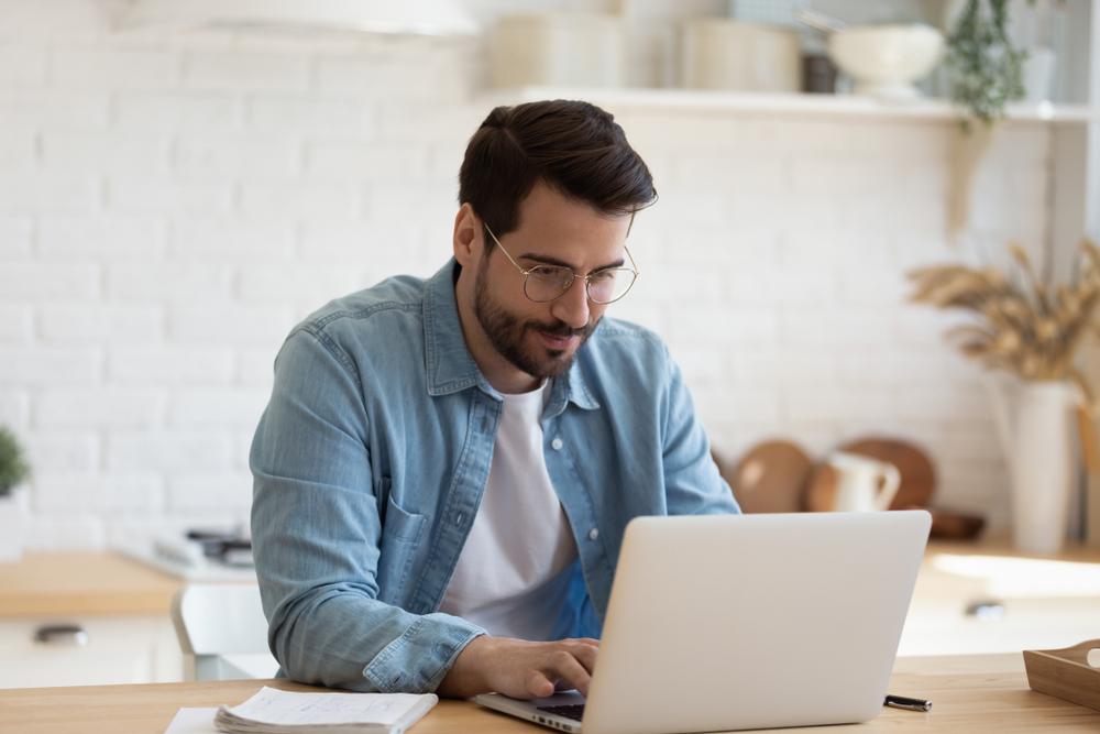 Vemos um homem no que parece ser a cozinha de sua casa. Concentrado, ele está mexendo em seu computador enquanto tem um caderno de anotações à esquerda (imagem ilustrativa). Texto: franquia Bioflora.