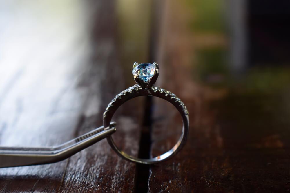 Vemos que alguém segura um anel com imitação de brilhante com uma pinça (imagem ilustrativa).