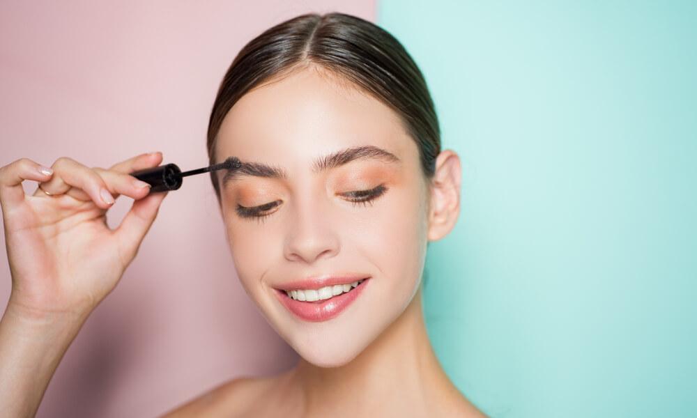 Vemos uma mulher se maquiar. Ela está utilizando uma máscara para sobrancelha (imagem ilustrativa). Texto: franquia de maquiagem bellaza.
