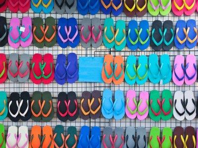Vários chinelos havaianas expostos em uma arara. Imagem ilustrativa texto franquia havaianas