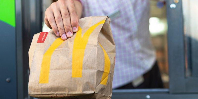 Mão masculina segurando pacote do mcdonalds no delivery. Imagem ilustrativa texto franquia mcdonald's