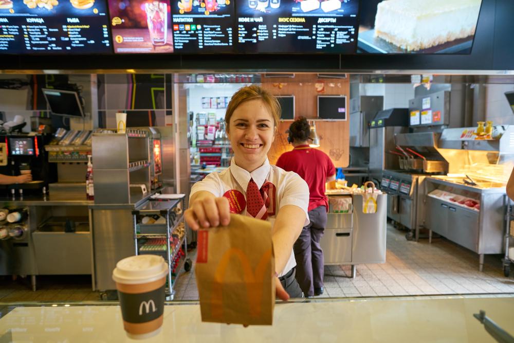 Vemos uma atendente do McDonald's entregando um lanche para viagem (imagem ilustrativa). Texto: franquia mc donald's.