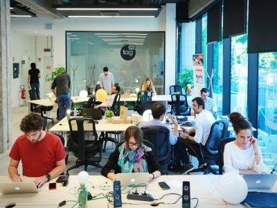 Várias pessoas em uma sala como num coworking. Imagem ilustrativa texto franquia Omie