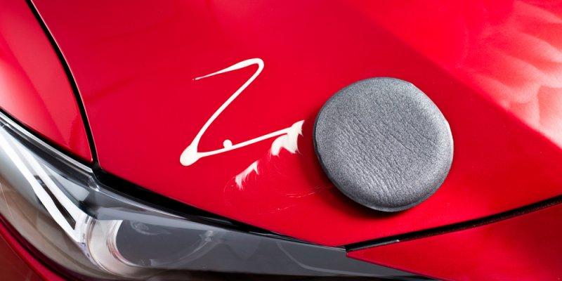 Capo de um carro vermelho com esponja e cera aplicada. Imagem ilustrativa texto franquia zaplus car.
