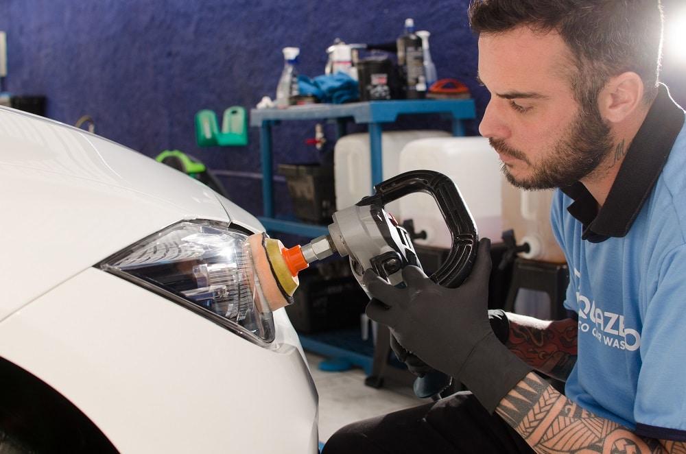 Vemos um técnico da Acquazero fazendo o polimento dos faróis do carro (imagem ilustrativa). Texto: franquia Zaplus Car.