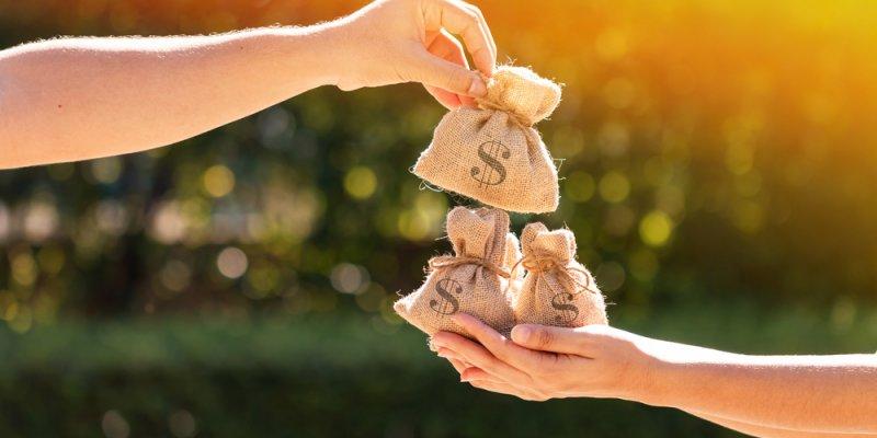 Mão segurando saquinhos de dinheiro e outra colando mais um junto as demais. Imagem ilustrativa texto franquias 20 mil
