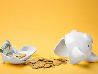 Cofre de porquinho quebrado no meio com moedas ao lado e fundo amarelo. Imagem ilustrativa texto franquias 40 mil