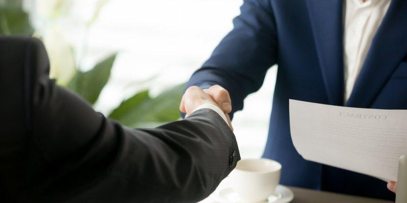 Homem apertando a mão de outro com um documento e xicara a frente. Imagem ilustrativa texto negócio online franquias do futuro