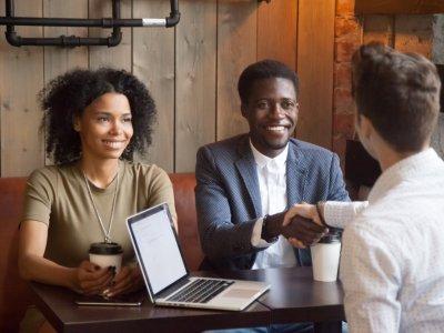 Casal de conversando com um homem. O homem acompanhado aperta a mão de outro fechando negócio. Imagem ilustrativa texto quanto custa formatar uma franquia