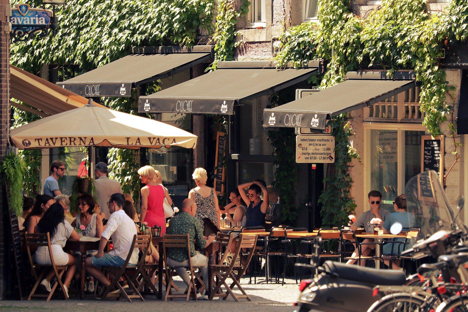 Vemos uma rua com vários bares e restaurantes; pessoas estão sentadas do lado de foras dos estabelecimentos (imagem ilustrativa). Texto: franquia Linked.