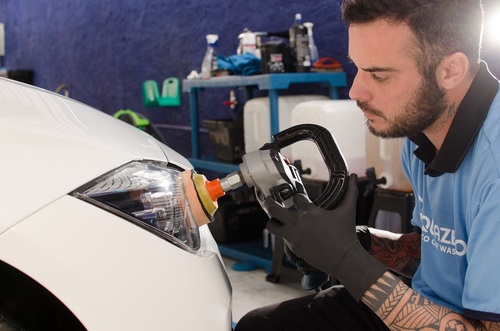 Vemos um técnico da A.cquazero fazendo a limpeza do farol de um carro (imagem ilustrativa). Texto: franquias 55 mil.