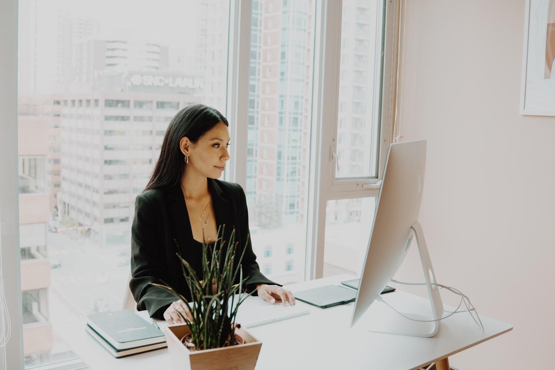 Vemos uma mulher sentada em seu escritório enquanto faz alguma coisa muito concentrada em seu computador (imagem ilustrativa). Texto: franquias de ensino.
