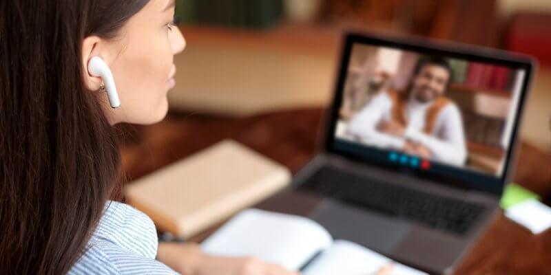 Mulher com caderno em frente ao computador durante uma chamada de vídeo. Imagem ilustrativa texto franquias de ensino