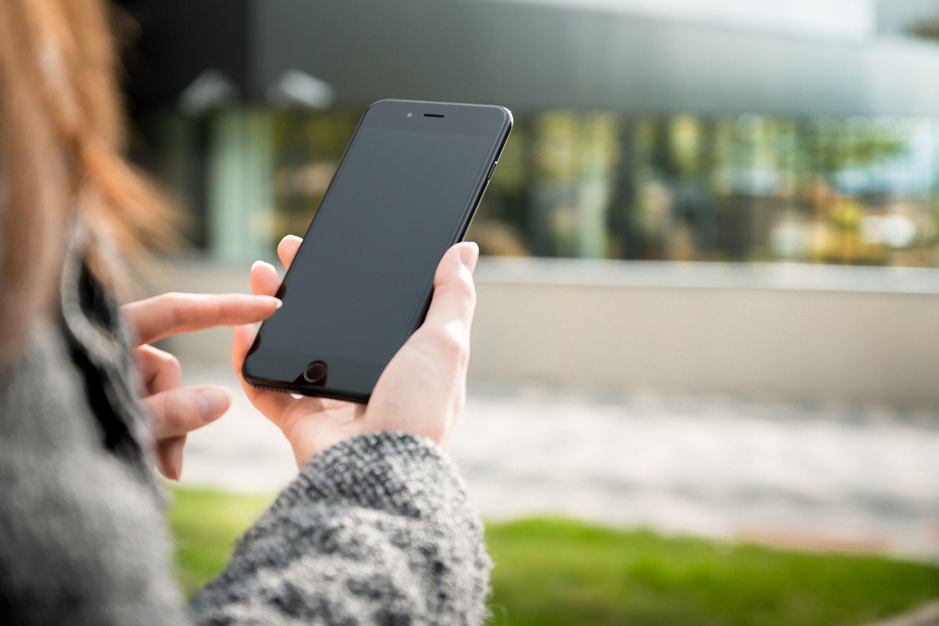 Vemos uma pessoa em um lugar amplo, usando um celular (imagem ilustrativa). Texto: franquias gastronomia.