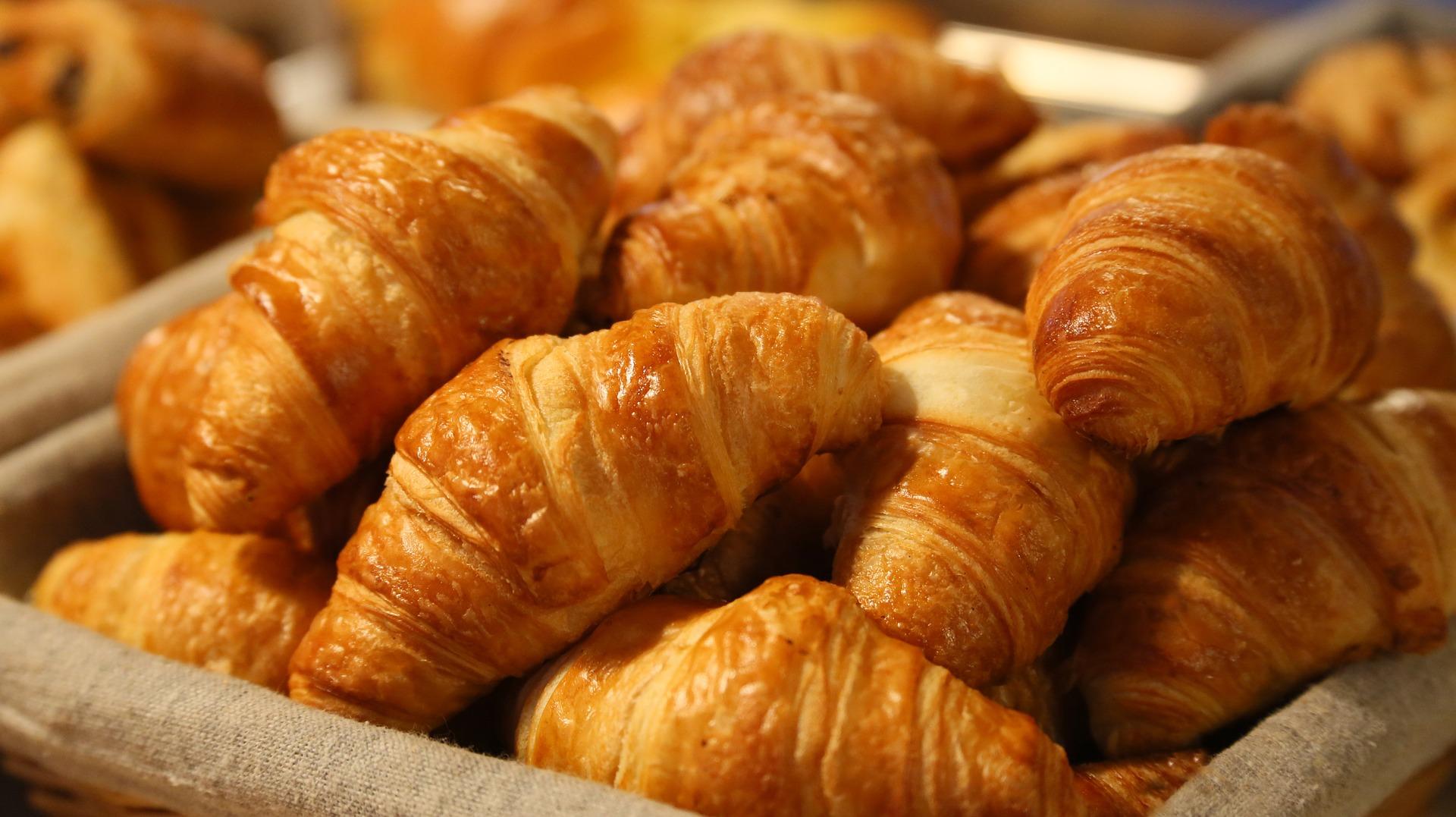 Vemos vários croissants em uma cesta (imagem ilustrativa). Texto: franquias gastronomia.