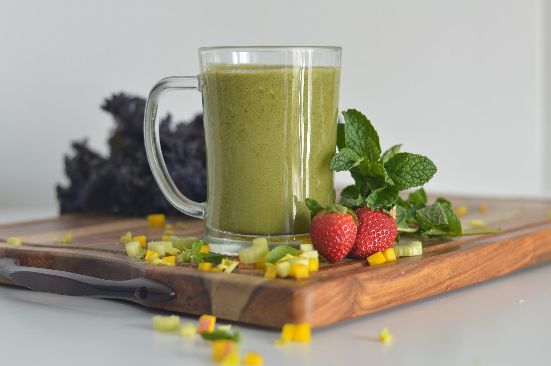 Vemos um copo com bebida verde e frutas ao lado (imagem ilustrativa). Texto: franquias gastronomia.
