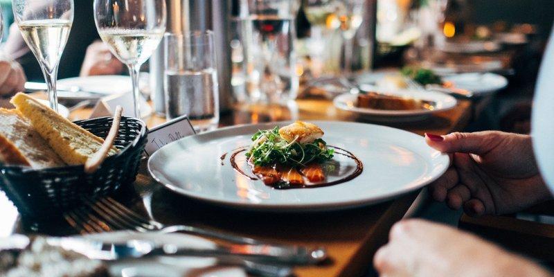 Foto de uma mesa com pratos, copos e comida. Imagem ilustrativa para texto franquias gastronomia.