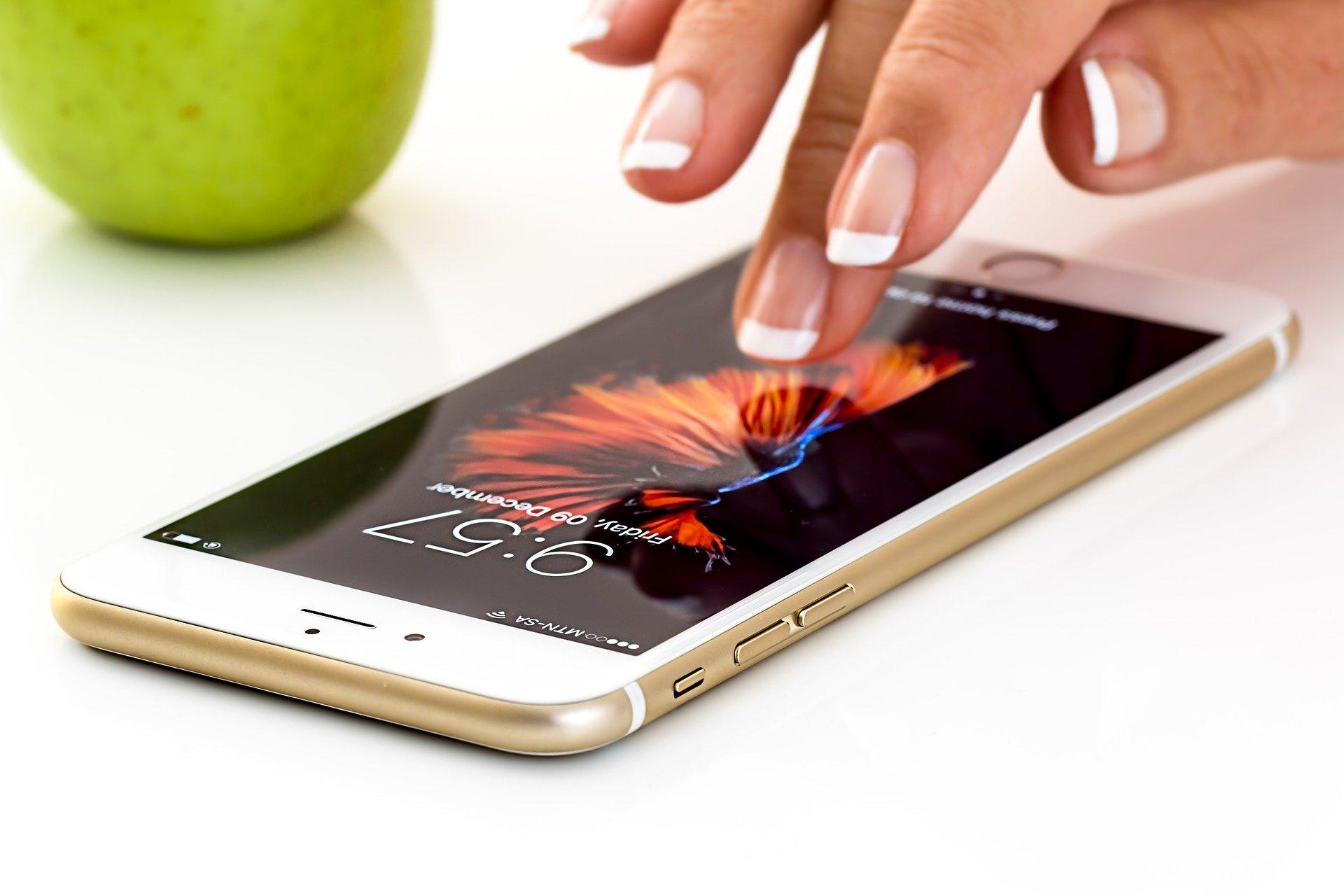 Vemos alguém prestes a tocar na tela de um smartphone que está sobre uma superfície branca (imagem ilustrativa).