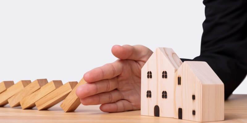 Mão masculina segurando a fila de domino caindo e protegendo uma maquete de casa de madeira. Imagem ilustrativa texto franquias ruins