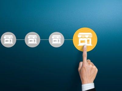 dedo apontando para um botão com loja desenhada e em amarelo. Imagem ilustrativa texto investimento franquia