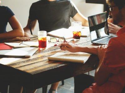 Foto de uma reunião de pessoas em uma mesa, com computadores, cadernos e bebidas. Imagem ilustrativa para texto empresa para formatação de franquia.