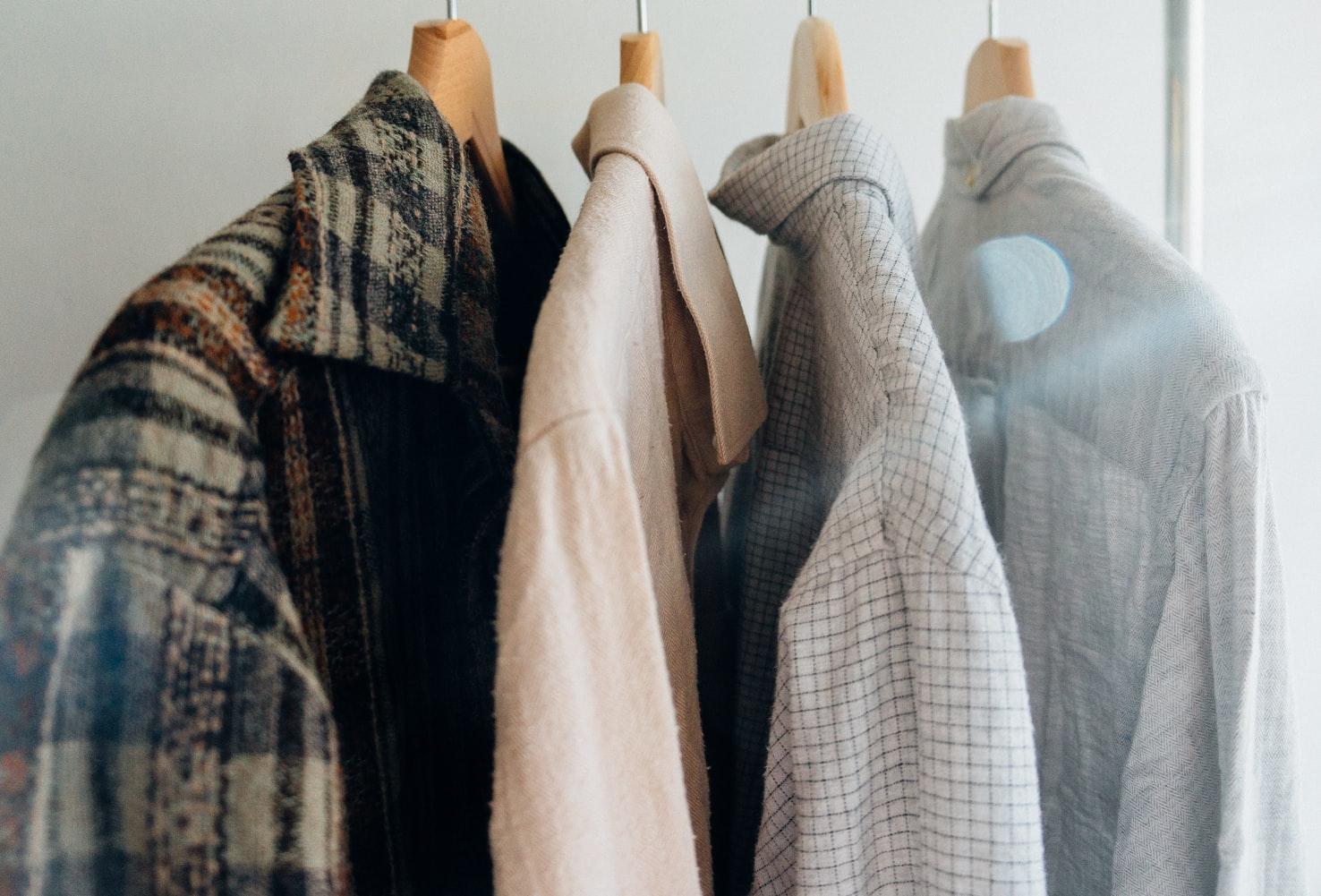 Vemos algumas roupas com ar de brechó penduradas em cabides (imagem ilustrativa).