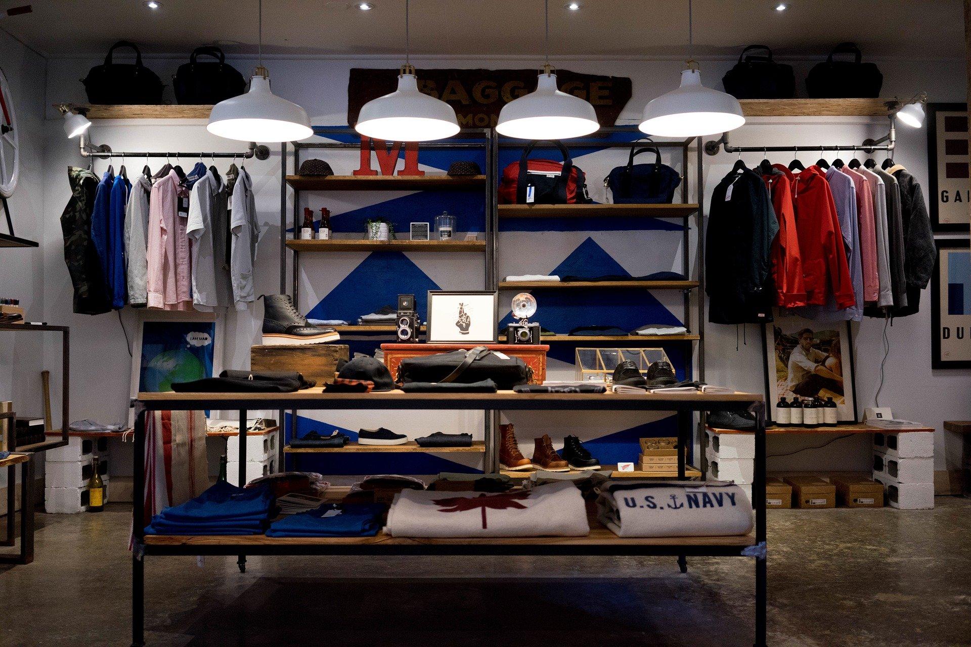 Vemos uma loja de roupas com várias araras e estantes (imagem ilustrativa). Texto: Franquia Hering Store.