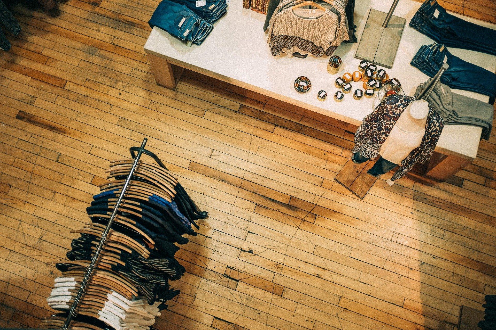 Vemos uma loja de roupa com balcão, manequins e araras (imagem ilustrativa).