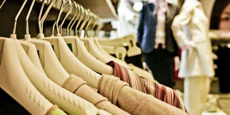 Foto de uma arara de roupas com manequins ao fundo. Imagem ilustrativa para texto Franquia Hering Store.