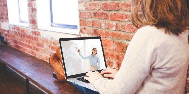 Foto de uma moça estudando com um computador no colo. Imagem ilustrativa para texto franquia prepara cursos.