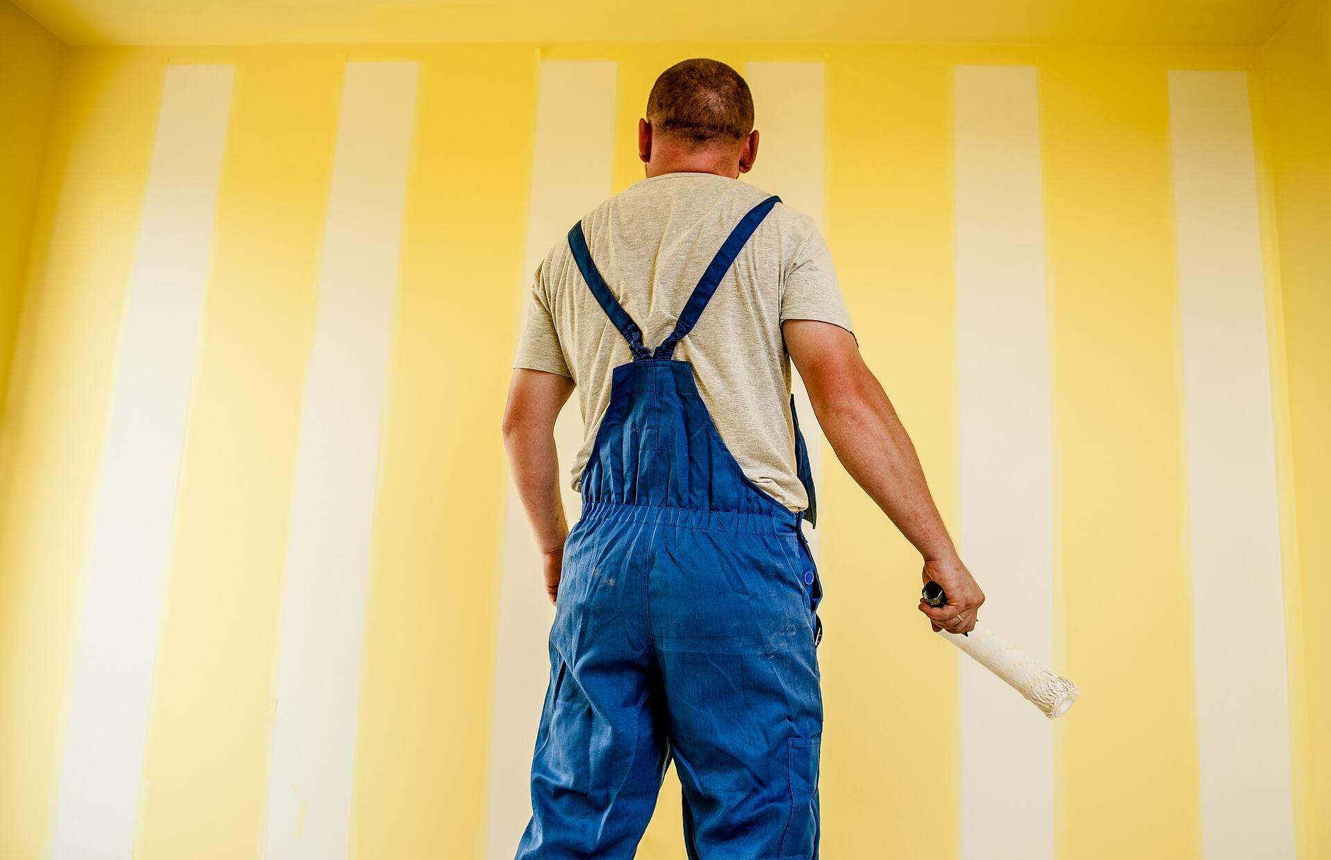 Vemos um homem pintando uma parede de amarelo (imagem ilustrativa). Texto: franquia reformas.
