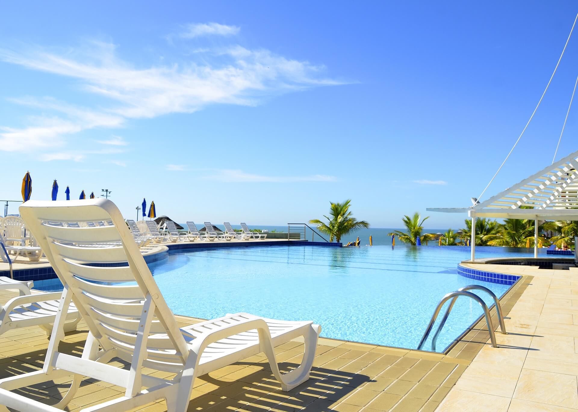Vemos uma grande piscina com cadeiras na beirada no que parece ser um hotel (imagem ilustrativa).