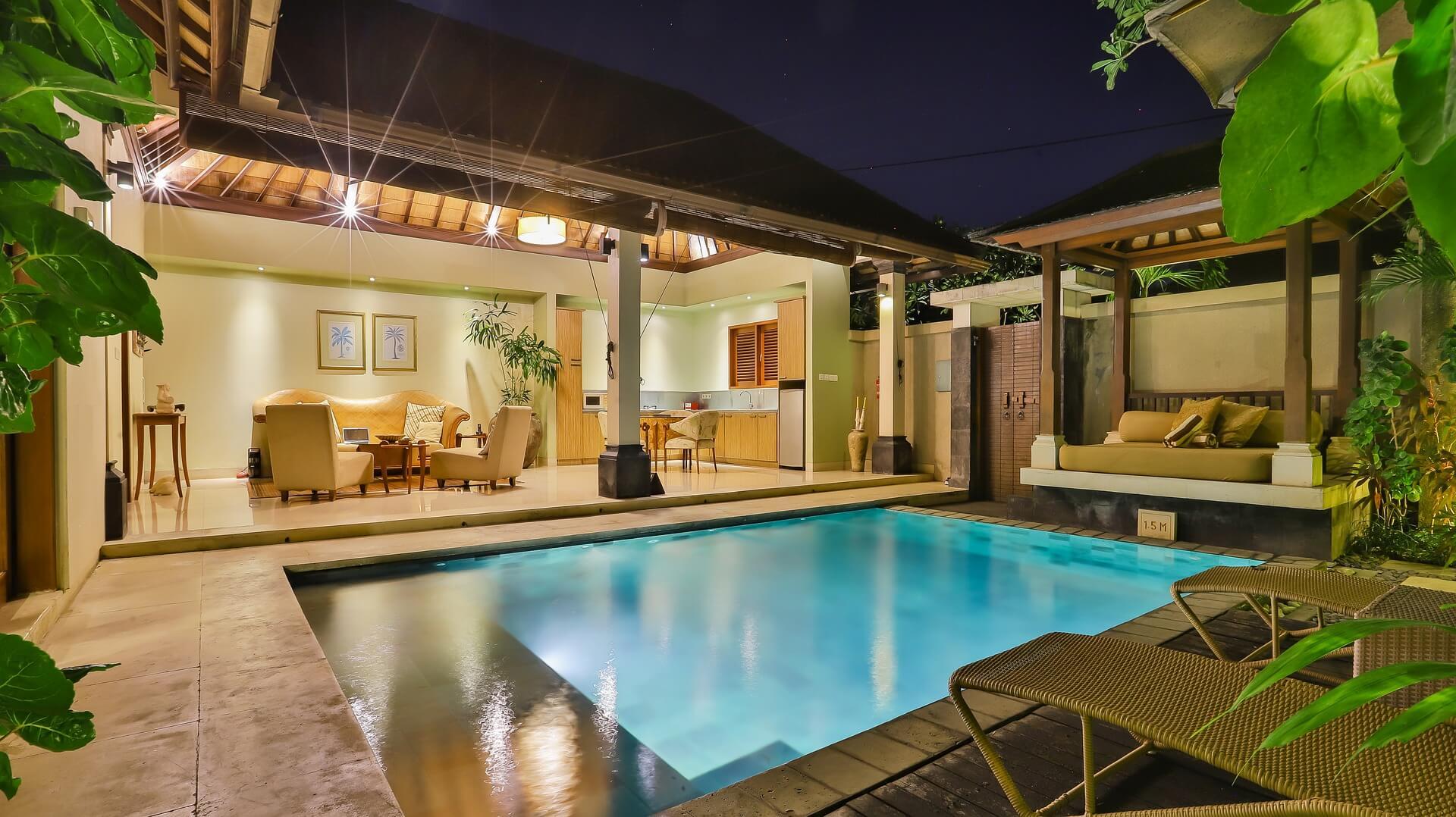 Vemos uma piscina na área externa com uma casa.