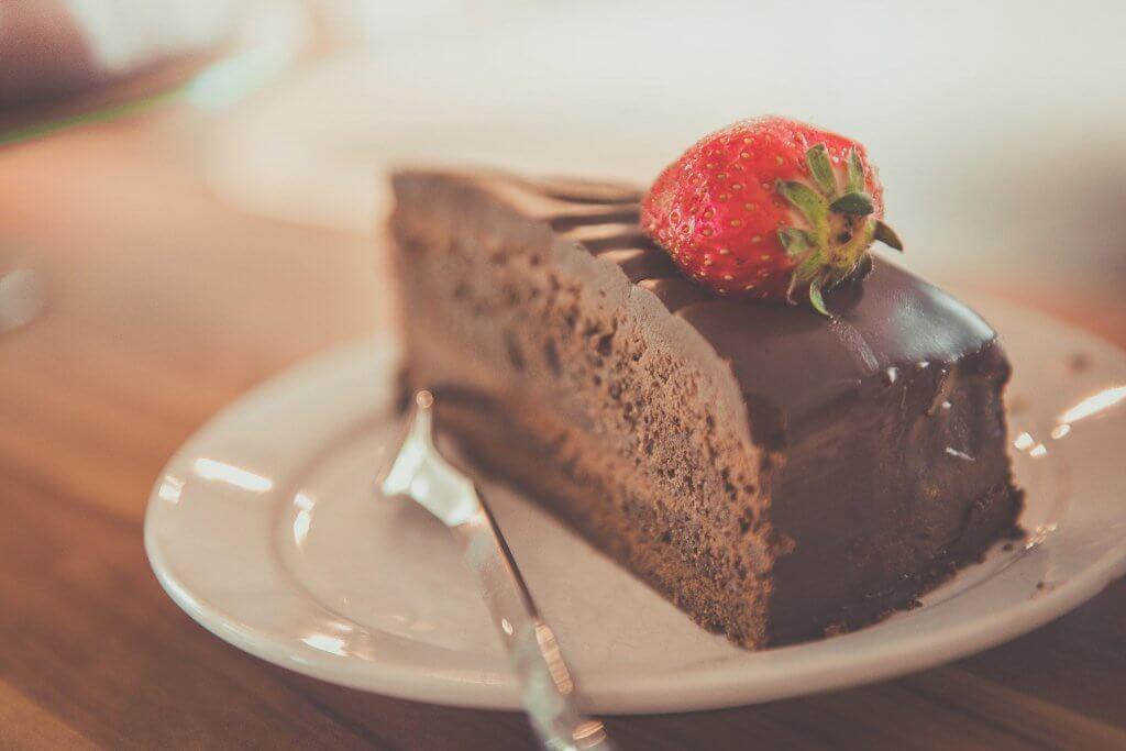 Vemos um pedaço de bolo de chocolate com morango em cima.