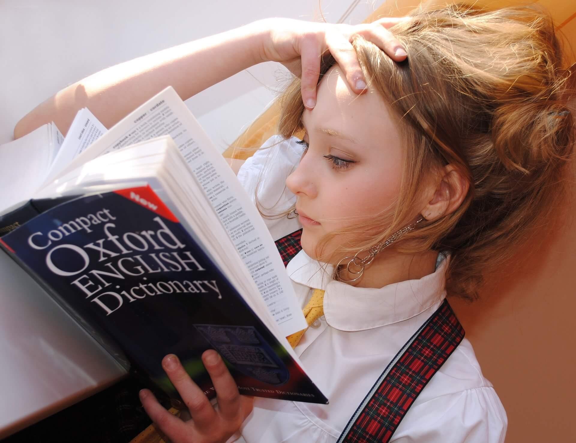 Vemos uma menina lendo um dicionário de inglês (imagem ilustrativa). Texto: franquias brasileiras.