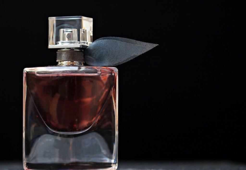 Foto de vidro de um perfume com laço de enfeite. Imagem ilustrativa para texto franquias brasileiras.