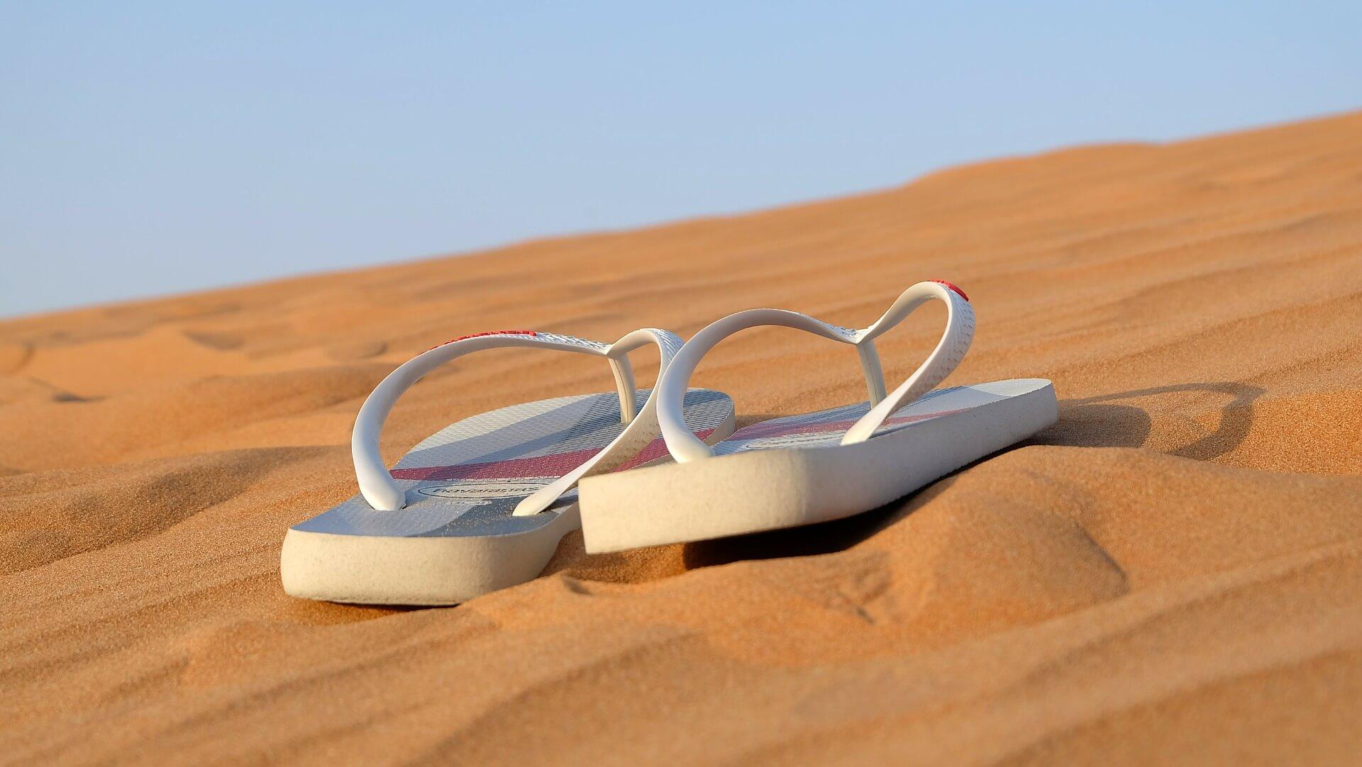 Vemos um par de chinelos no meio da areia (imagem ilustrativa).