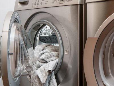 Foto de uma máquina de lavar aberta com uma peça de roupa na entrada. Imagem ilustrativa para texto microfranquia de lavanderia #1Lavanderia.