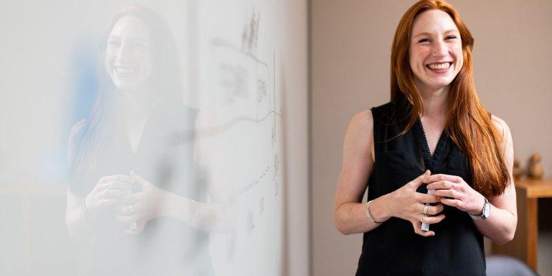 Foto de uma mulher com roupa preta fazendo uma apresentação. Imagem ilustrativa para texto empreendedorismo feminino.