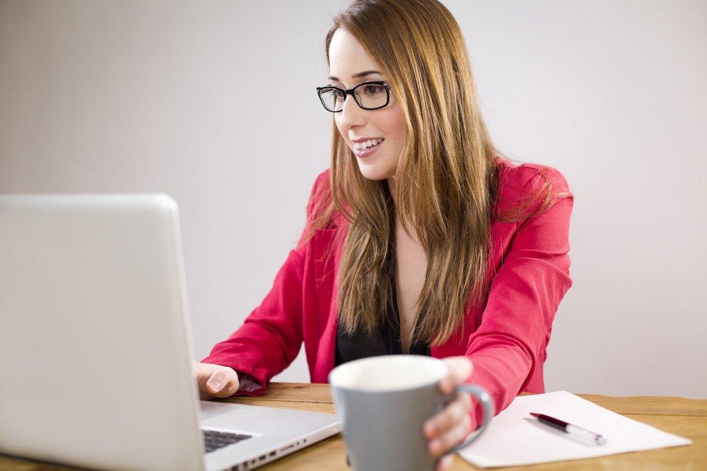Foto de uma mulher usando computador e segurando uma xícara de café.