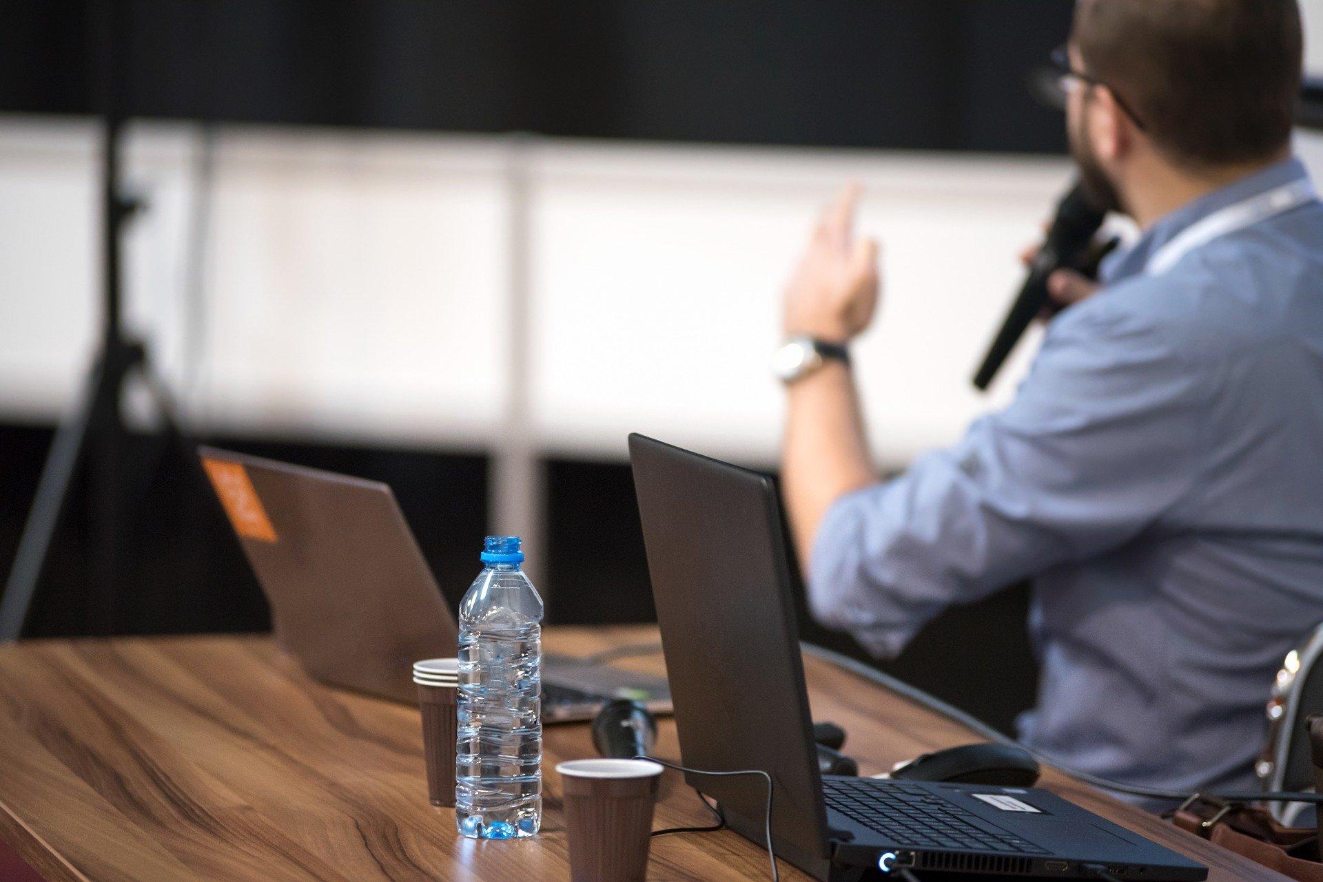 Vemos um homem falando ao microfone próximo de uma mesa com vários computador (imagem ilustrativa). Texto: feira de franquia.