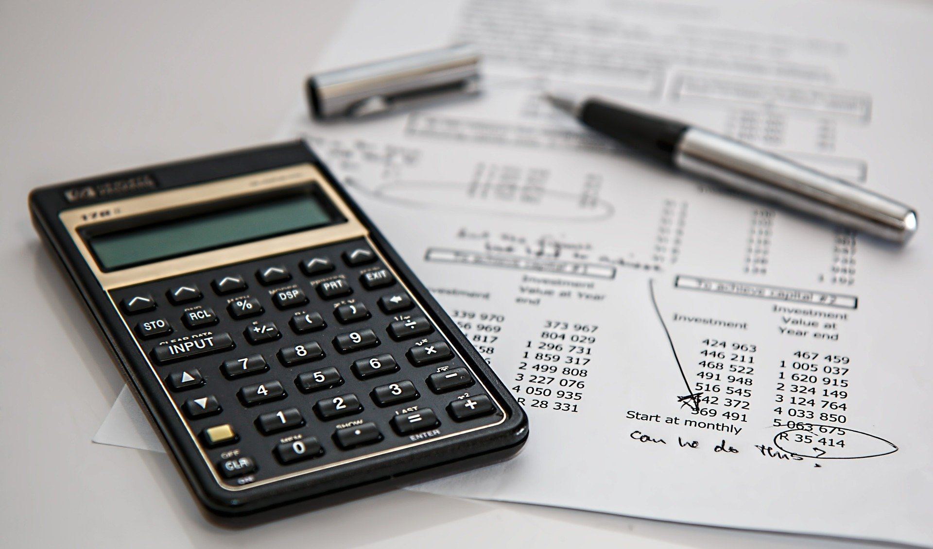 Vemos, sobre um papel com vários números impressos, uma calculadora e uma caneta destampada (imagem ilustrativa).