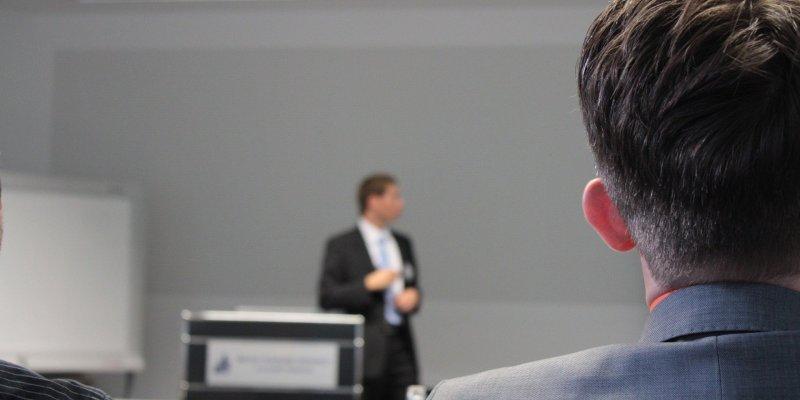 Foto de um homem palestrando com pessoas assistindo. Imagem ilustrativa para texto feira de franquia.