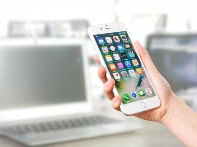 Imagem de uma mão segurando um celular com vários aplicativos na tela. Imagem ilustrativa texto franquia de aplicativo delivery.
