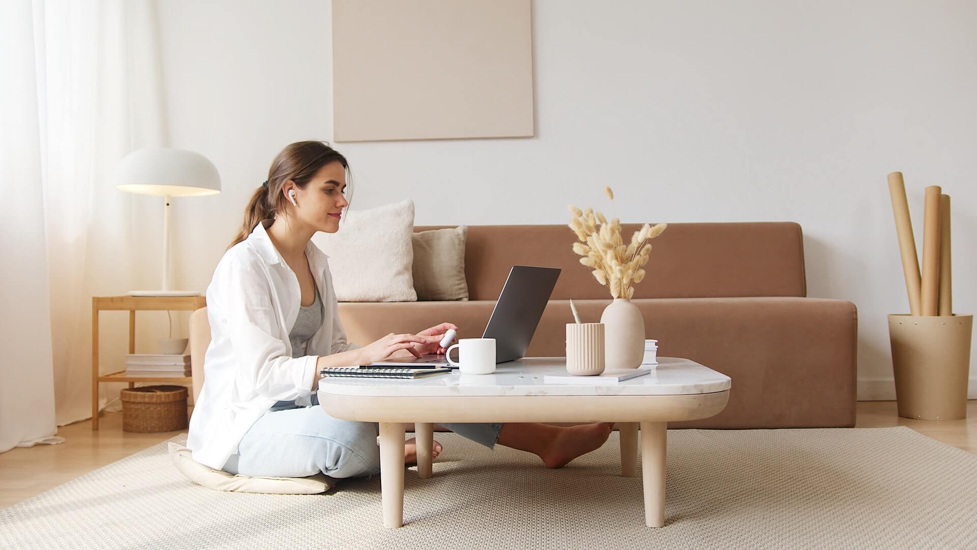 Vemos uma mulher sentada na sala de casa enquanto tem aulas on-line na frente de computador (imagem ilustrativa). Texto: franquia de educação qualifica cursos.